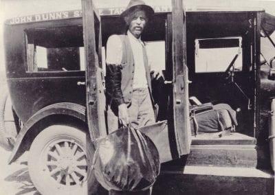 John Dunn unloading taxi service baggage in Taos, 1927